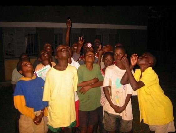 Photo of students in Uganda looking up into the night sky